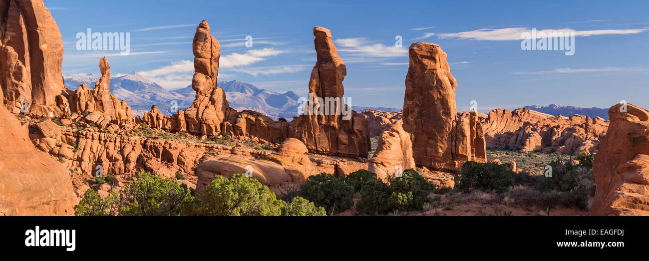 Panorama of four 'Marching Men' sandstone pillars in front of the La Sal Mountains in the Klondike Bluffs - Stock Image