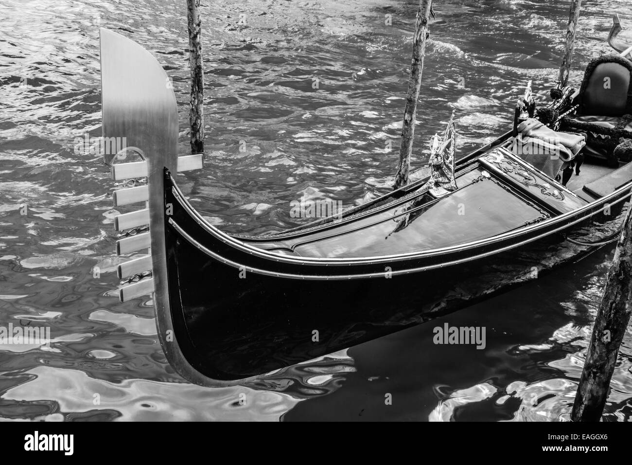 Black and white shot of a gondola docked in Venice - Stock Image