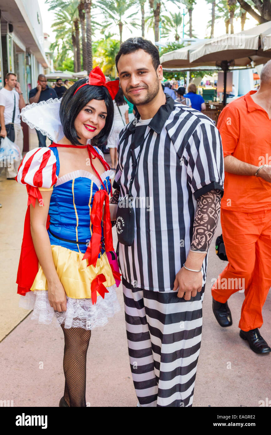 miami beach florida lincoln road pedestrian mall halloween costume wearing outfit character snow white prisoner stripes man woman couple