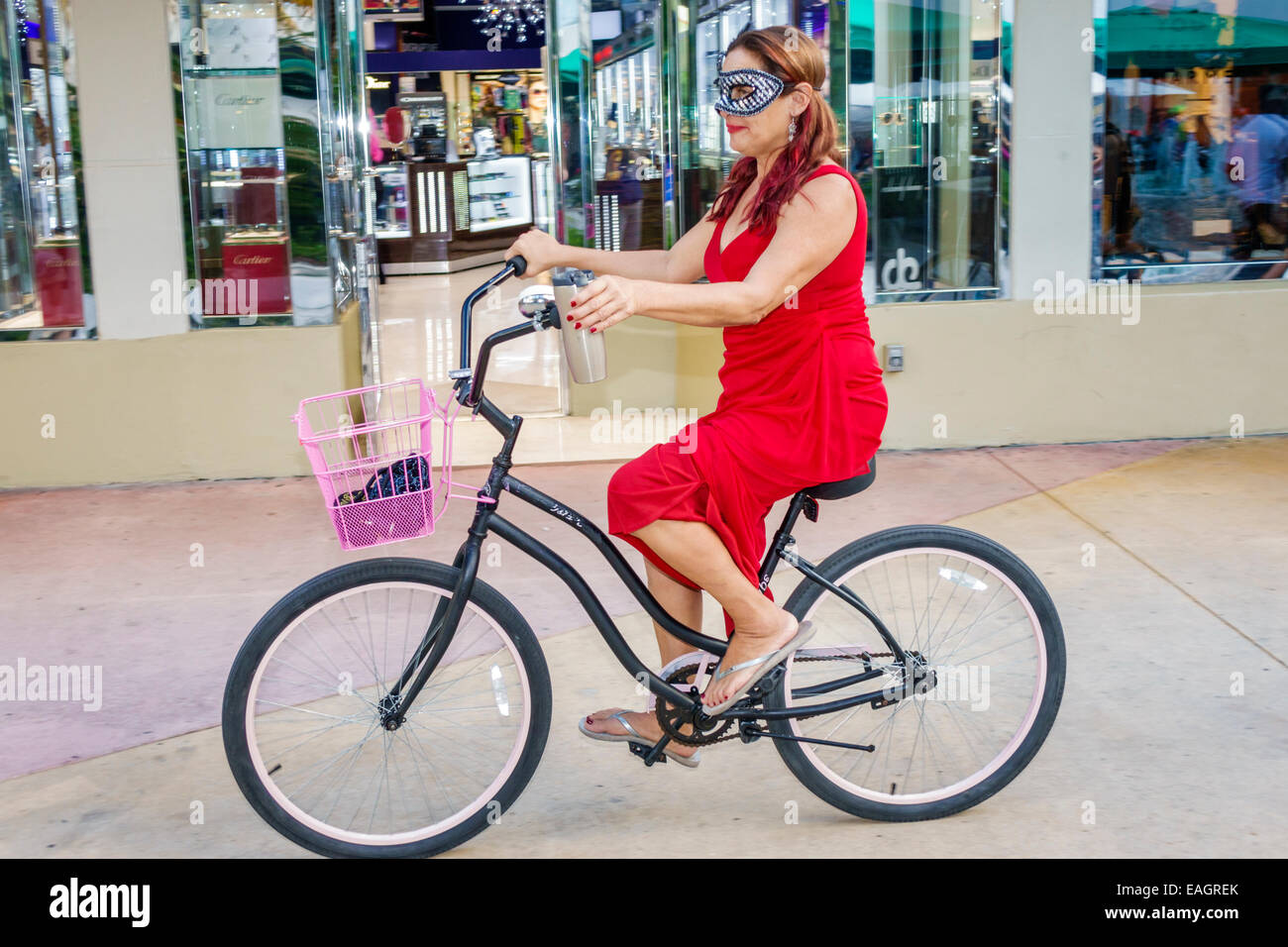 Miami Beach Florida Lincoln Road pedestrian mall Halloween costume wearing outfit character woman mask riding bicycle - Stock Image