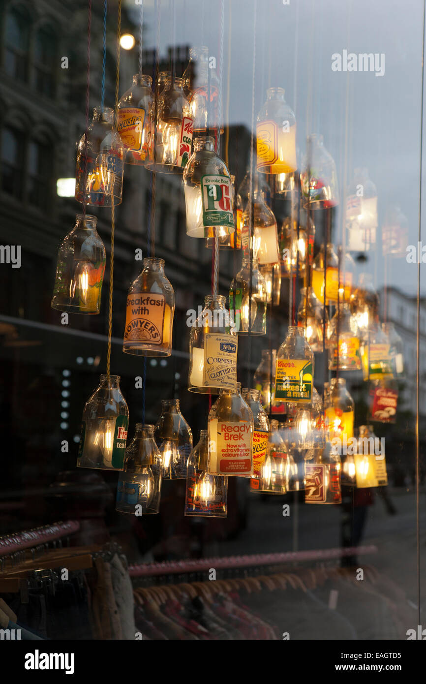 'Cow' clothing store with illuminated broken glass bottles as lamp shades creating Art Deco appearance, - Stock Image