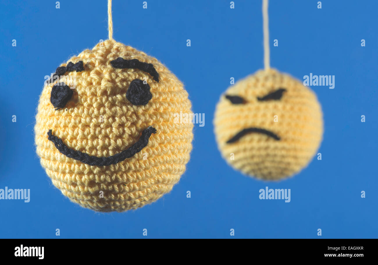 Knitted yellow emoticons on blue background - Stock Image