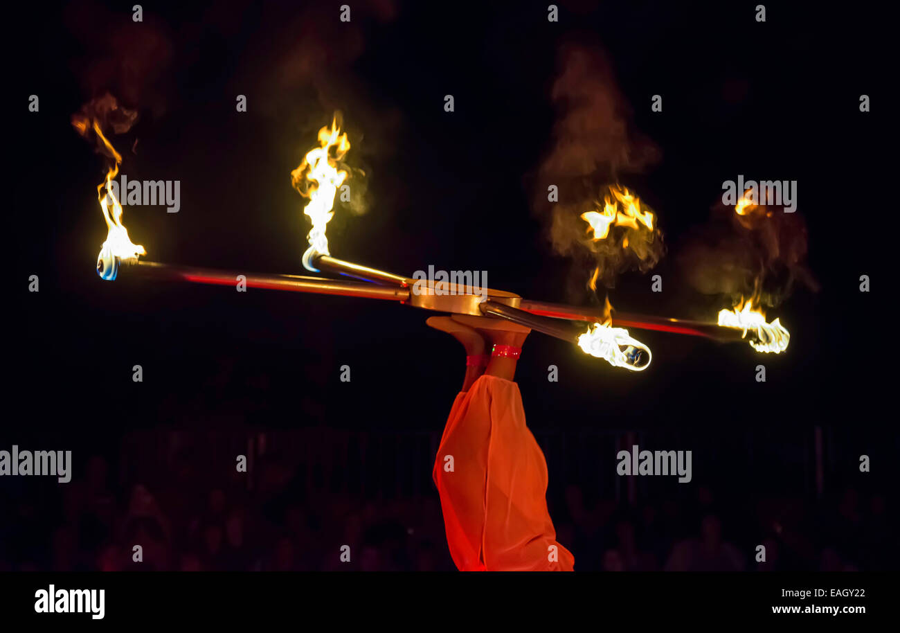 Juggler in the circus juggling with fire - Stock Image