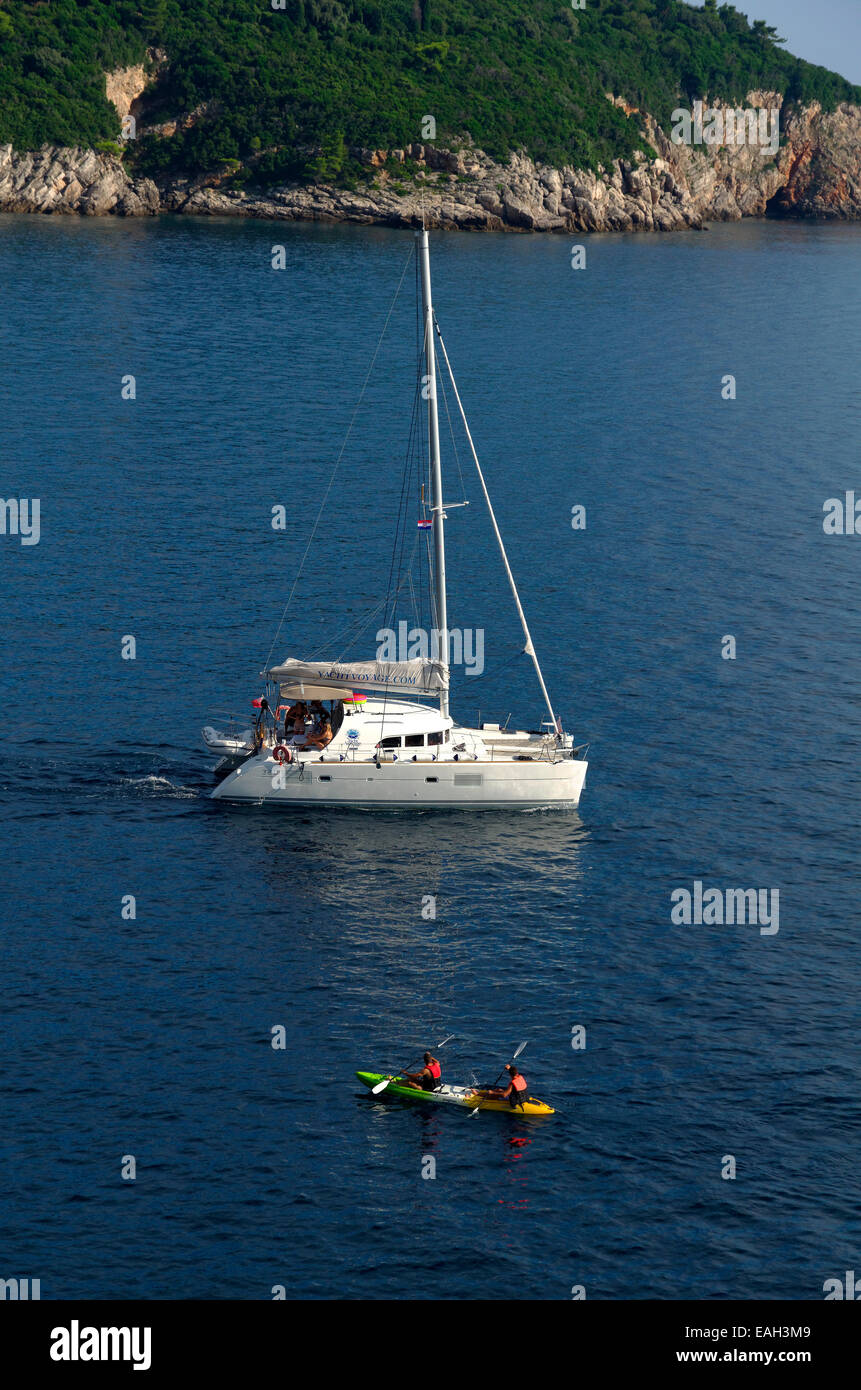 UK registered catamaran sailing yacht cruiser motoring in Croatia. Canoeists in foreground. Yacht Voyage.com livery - Stock Image
