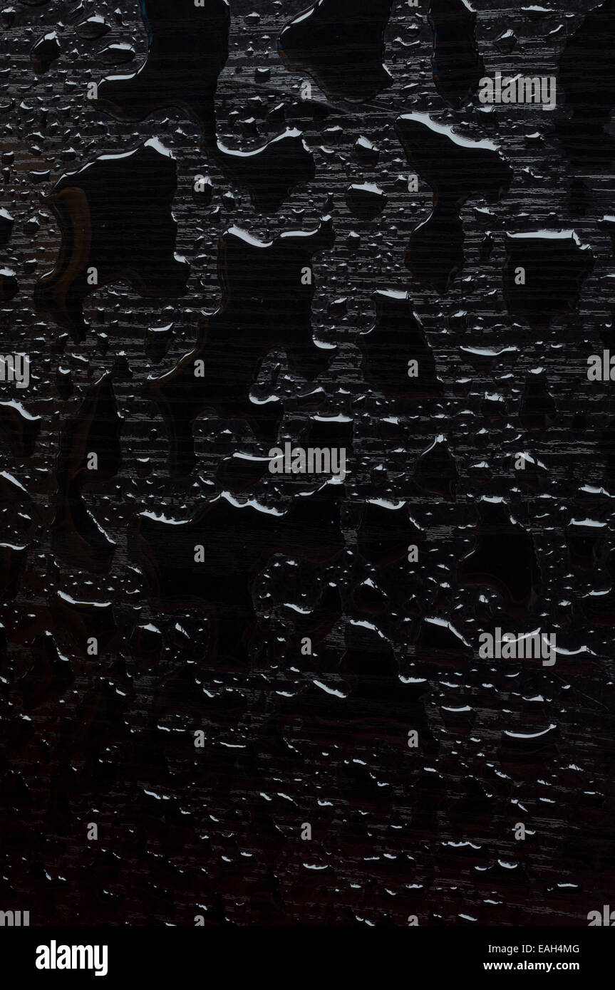 Texture of water drops on a black wooden base - Stock Image
