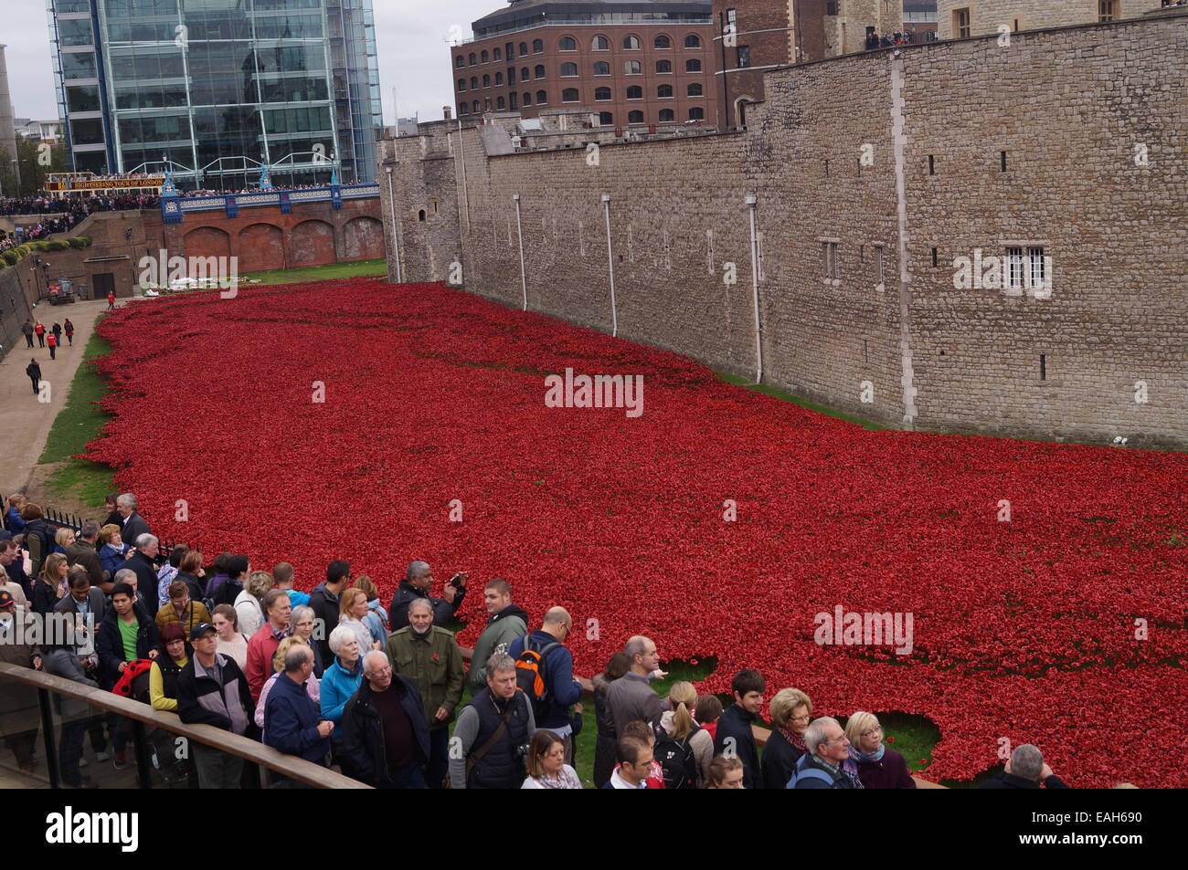 Visitors to the Tower of London view the art installation 'Blood Swept Lands and Seas of Red' in commemoration - Stock Image