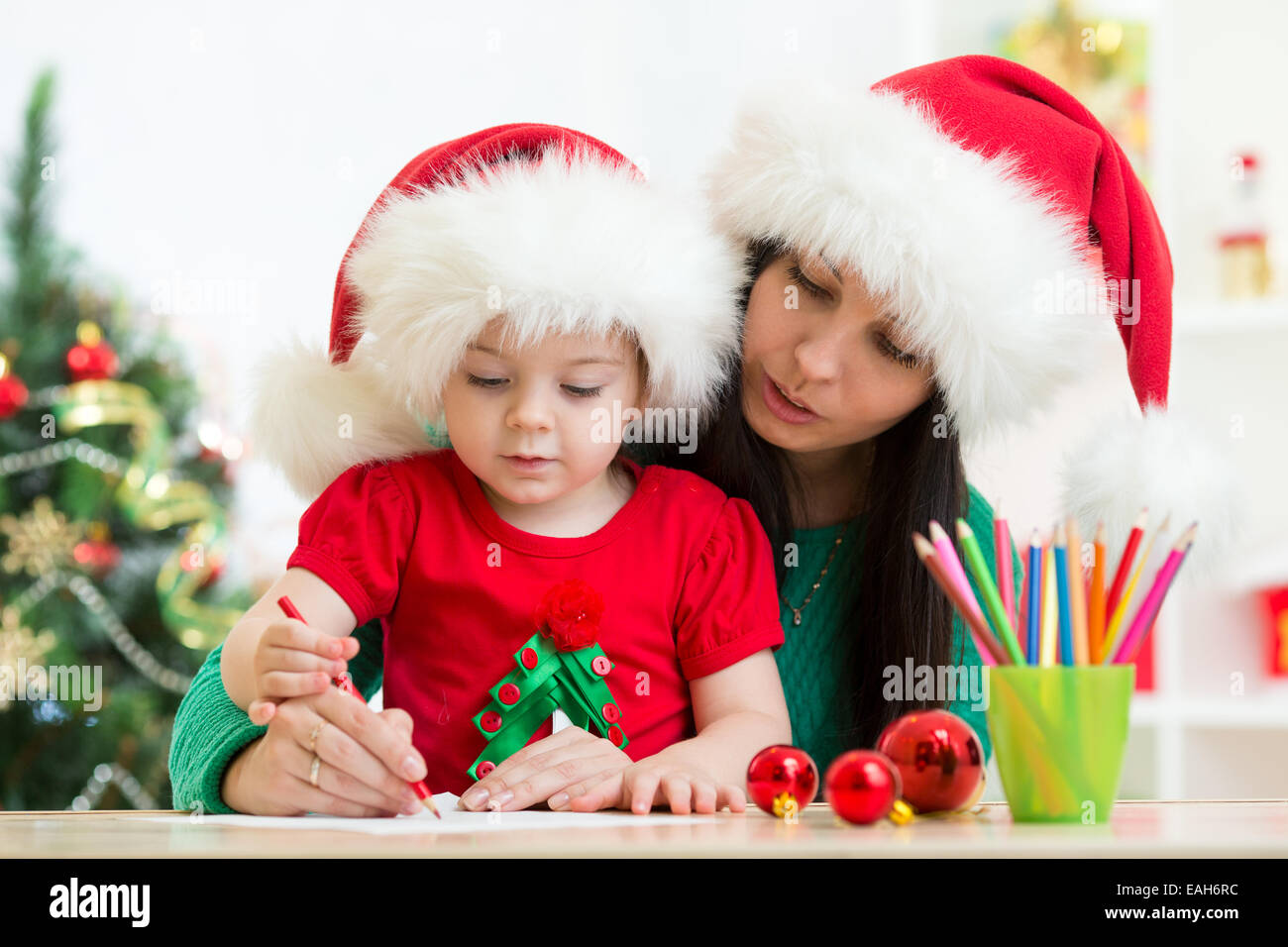 child girl and mother writing christmas letter to santa stock photo