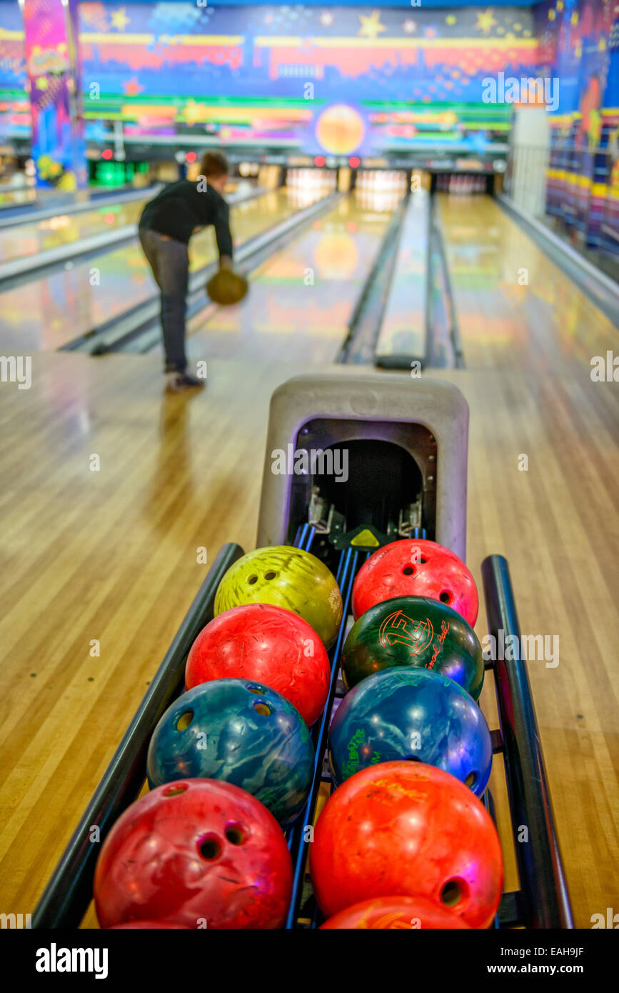 Bowling balls and silhouette of player on blurred background - Stock Image