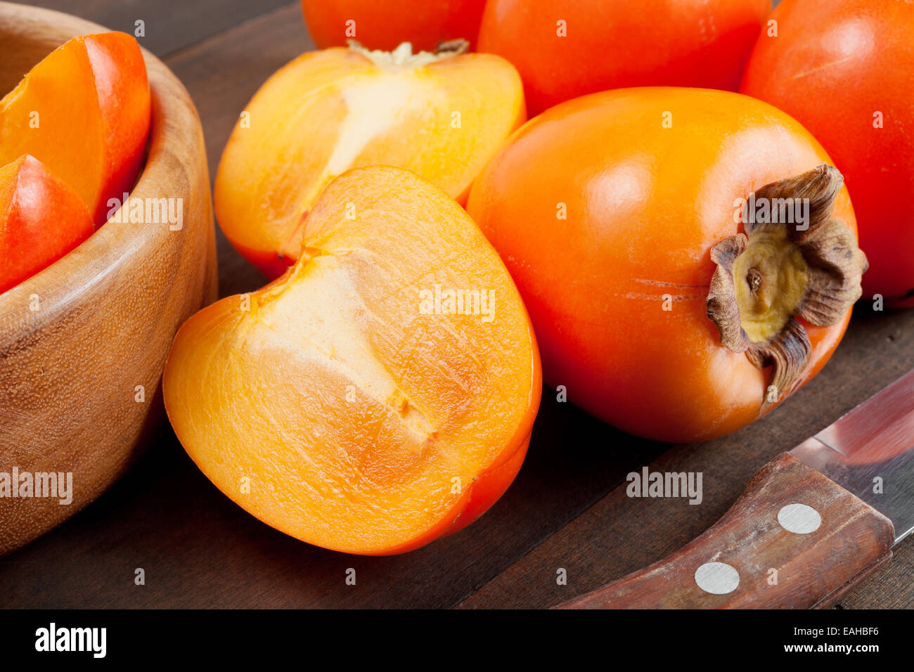 persimmons on wooden table - Stock Image