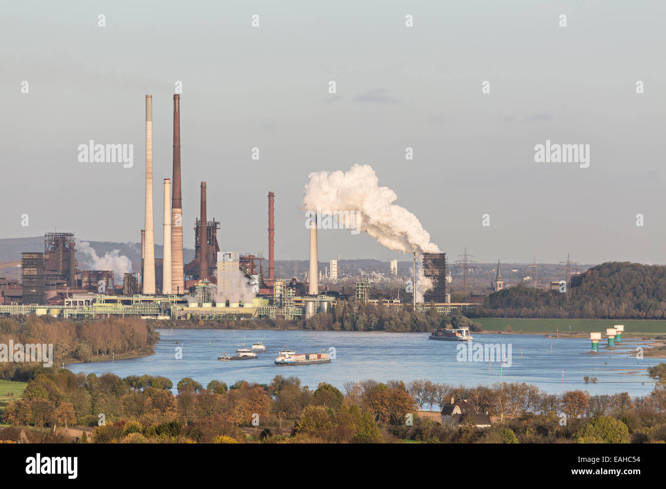 Steaming Coking Plant at the river Rhine near Duisburg, Germany with some ships on the river. - Stock Image