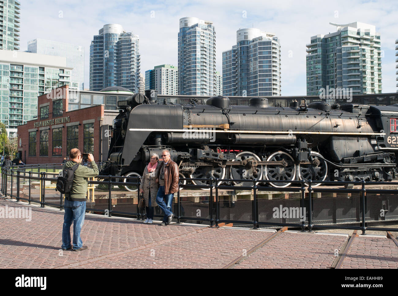 Couple being photographed before steam train 6213 on turntable at John Street Roundhouse, Toronto, Ontario, Canada - Stock Image