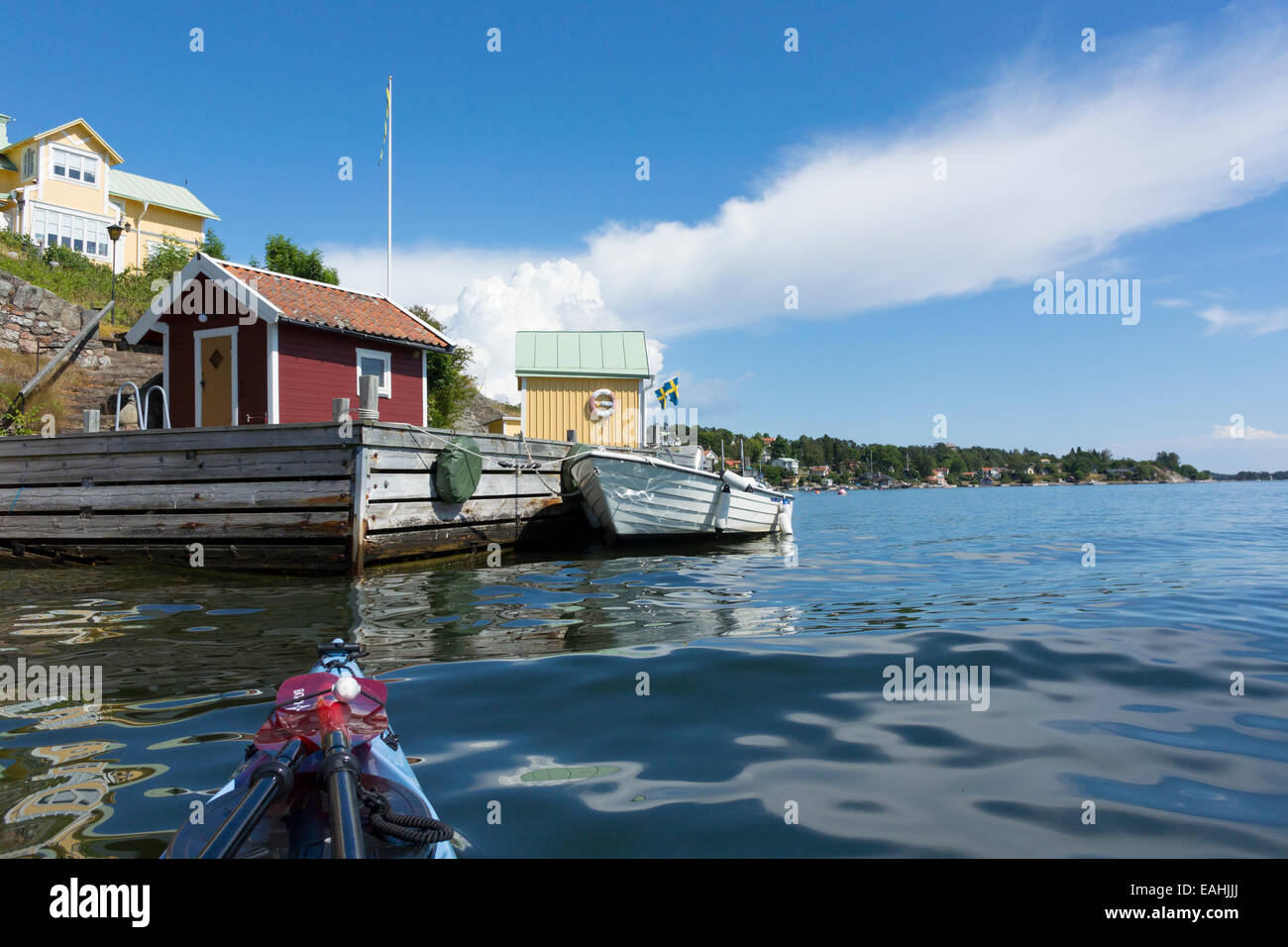 A boat house and recreational boat at Dalarö in the Stockholm archipelago viewed from a sea kayak. - Stock Image