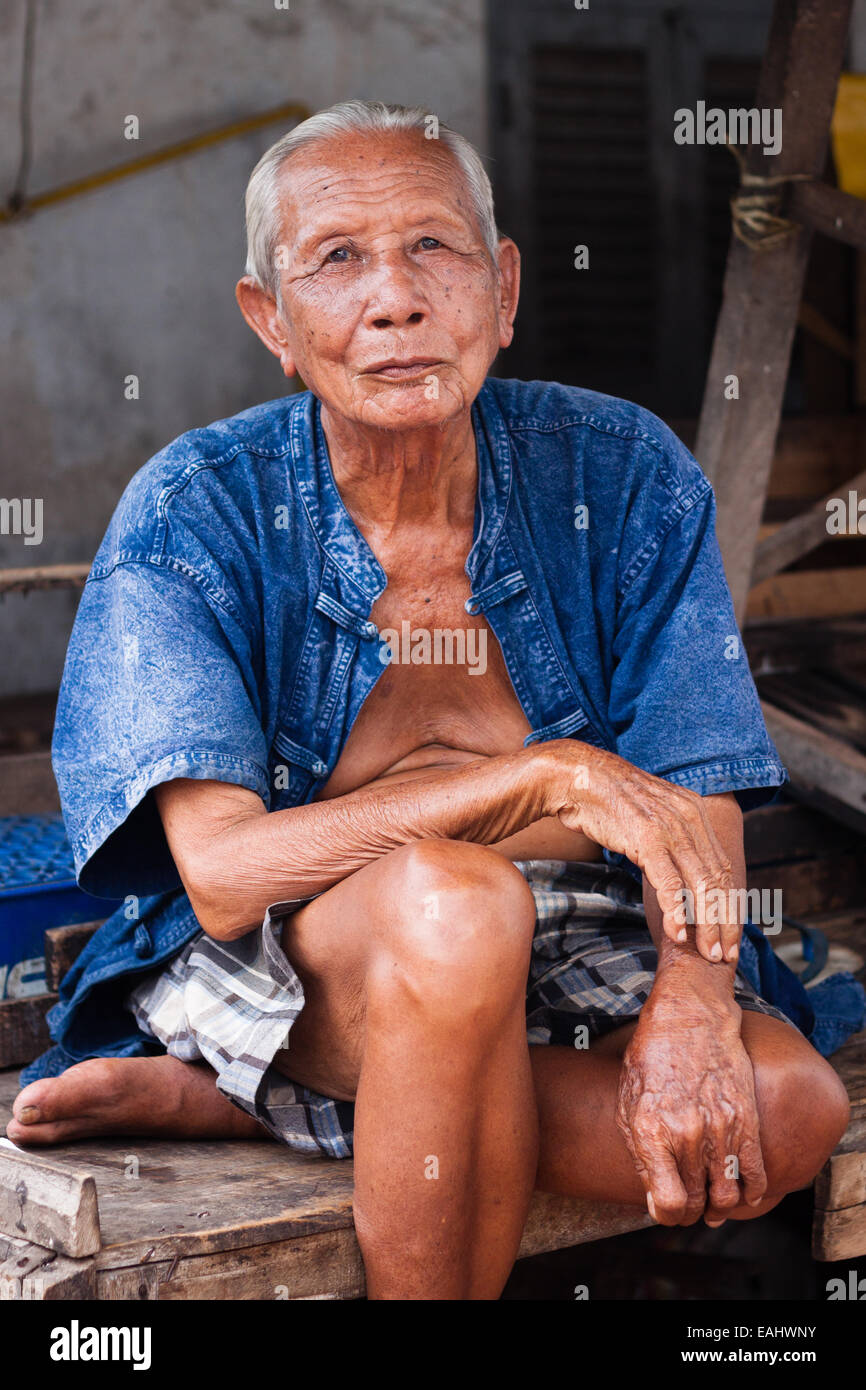 An elderly man near the market in the Lao town of Luang Prabang - Stock Image