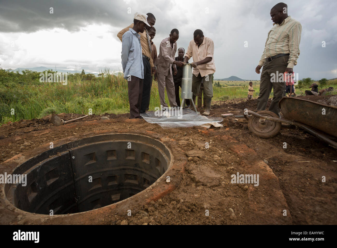 Community members in Kaptali Lower village, Bukwo District, Uganda work to construct a shallow well in their community. - Stock Image