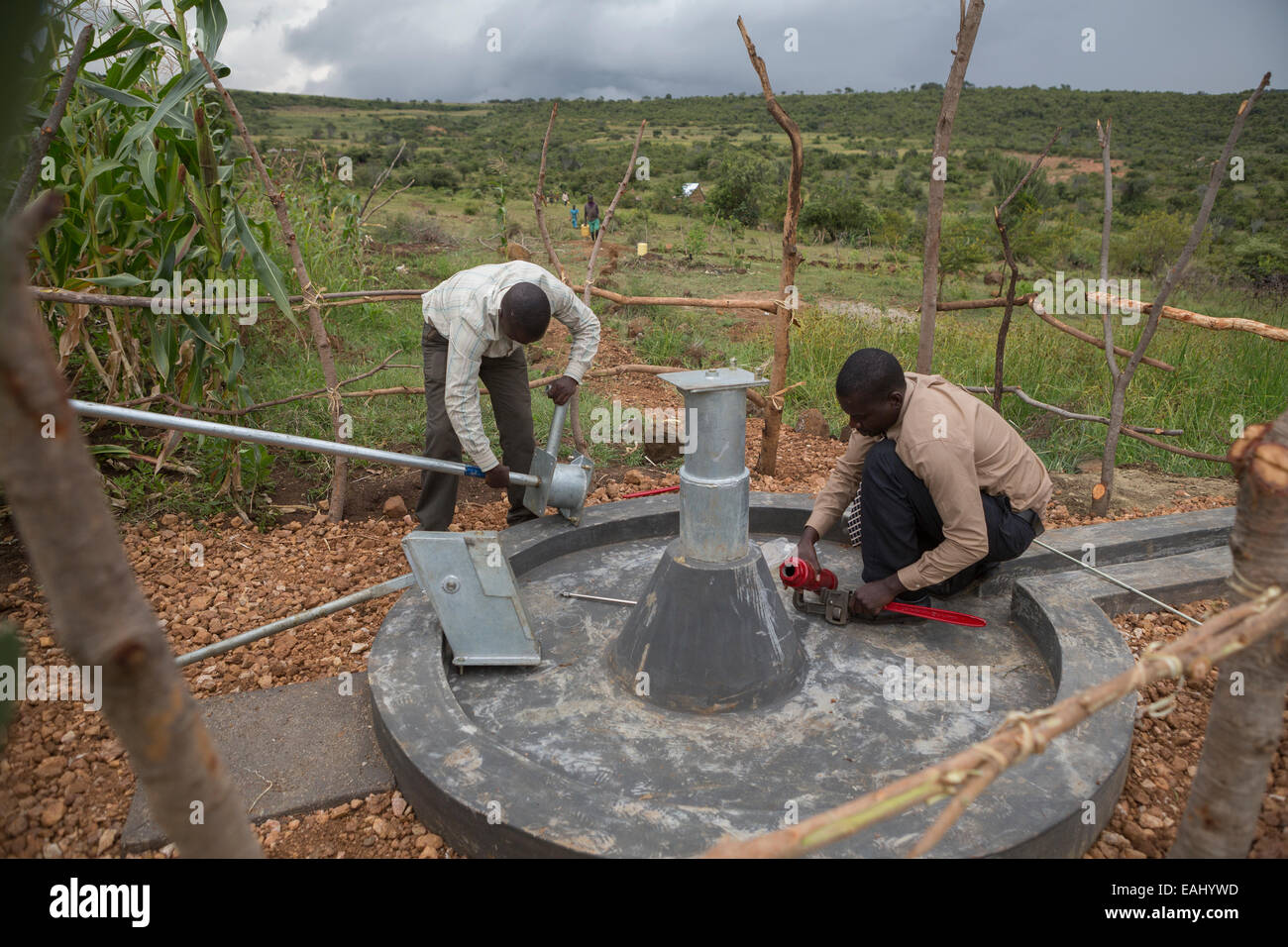 Community members in Sukuroi village, Bukwo District, Uganda work to construct a shallow well in their community. - Stock Image