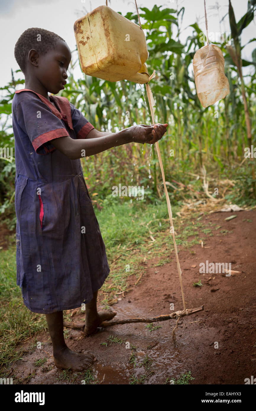 A young girl washes her hands using a tippy-tap in Bukwo District, Uganda, East Africa. - Stock Image