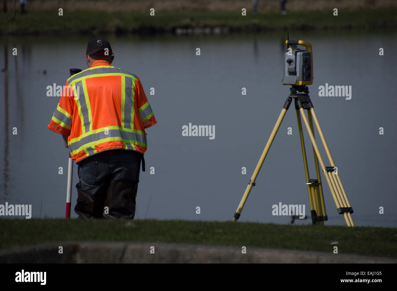 A surveyor by a lake. - Stock Image