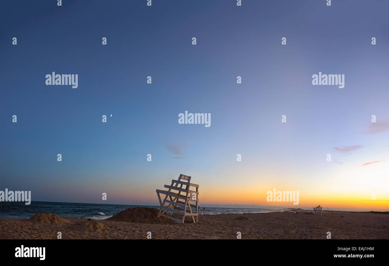 Summer in the Hamptons. Ponquogue Beach, Hampton Bays, New York blue hour sunset lifeguard chairs, sliver of the - Stock Image