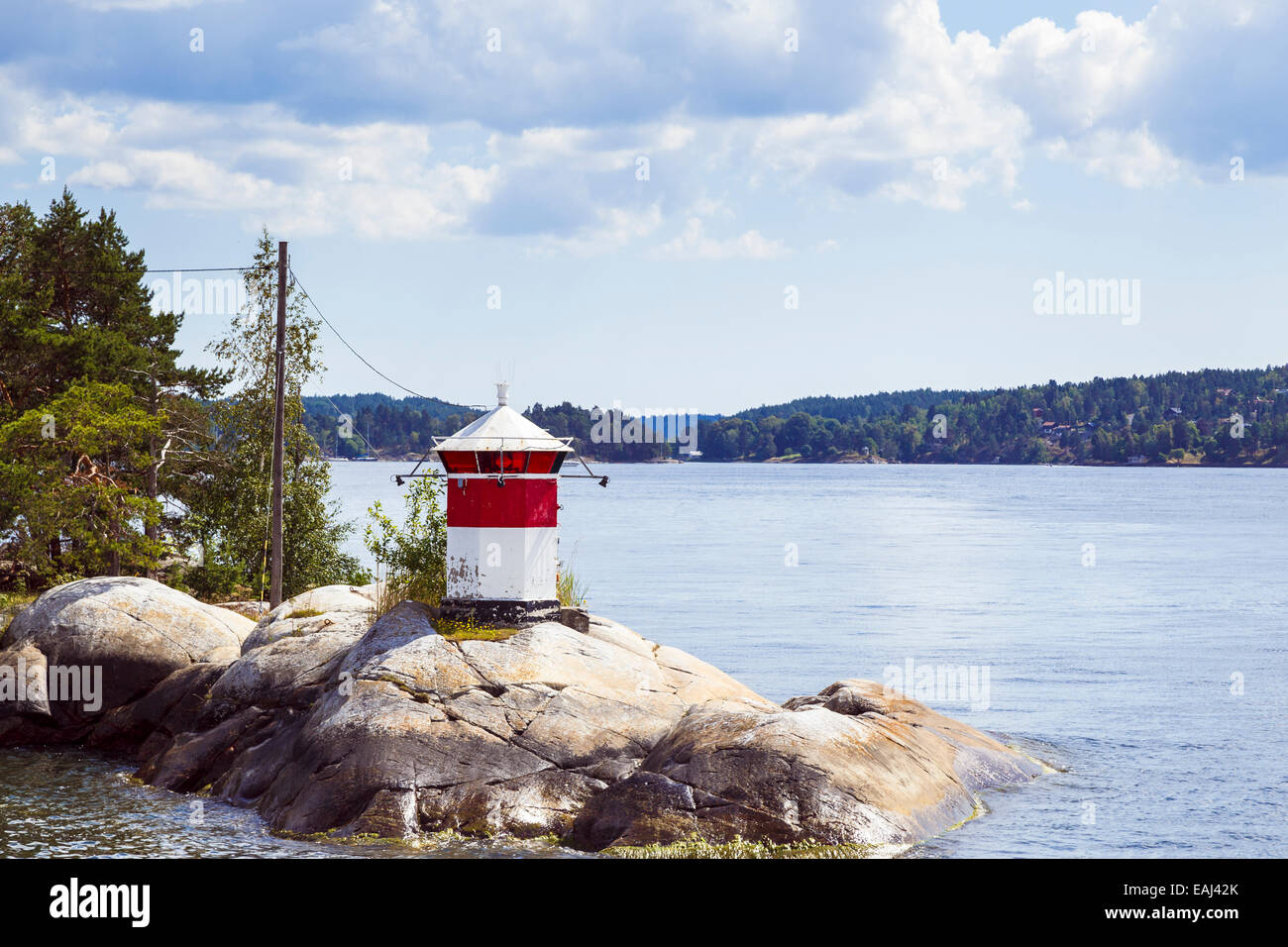 Small red and white lighthouse in Stockholm archipelago, Sweden, Sweden - Stock Image