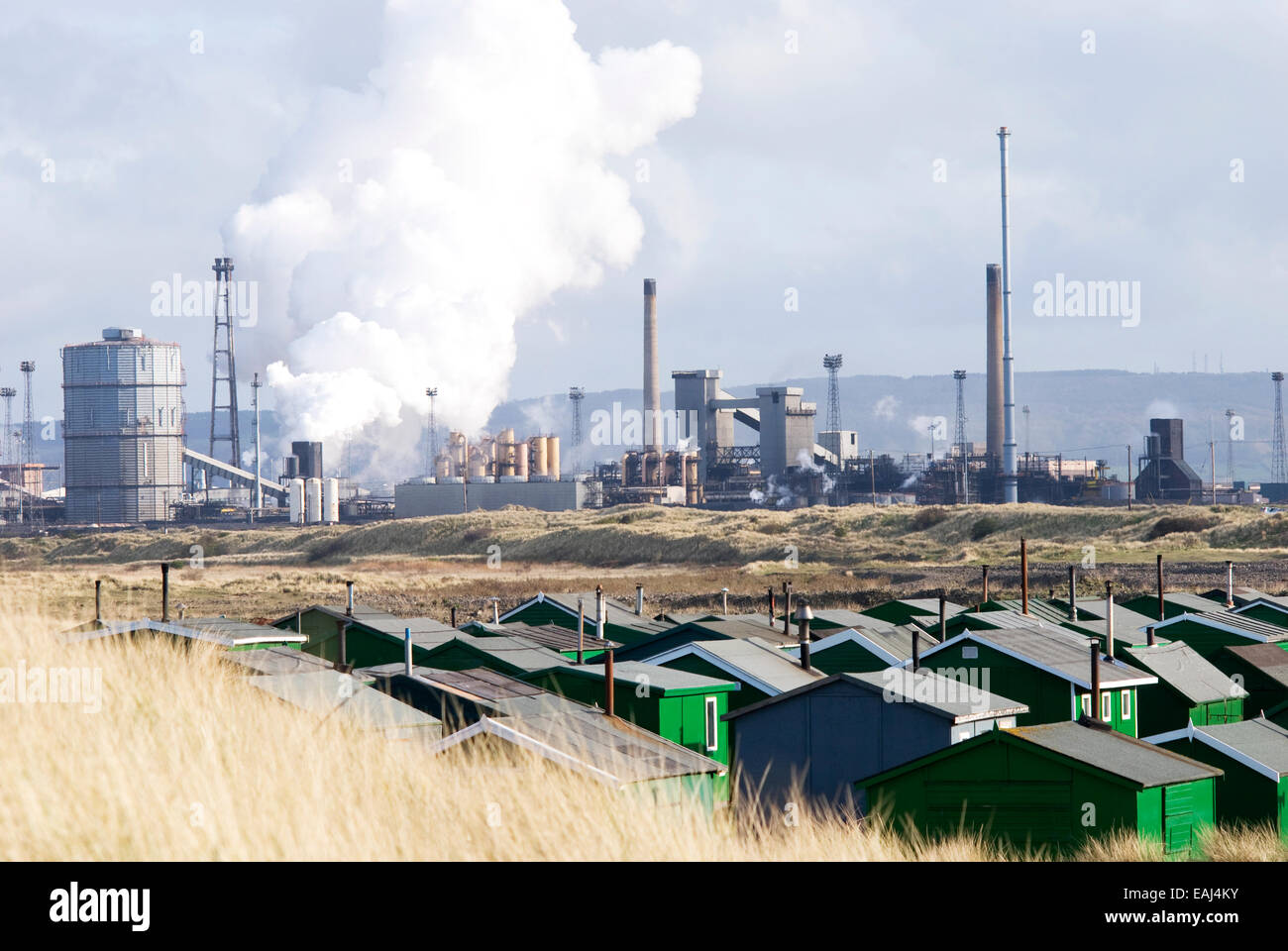 Green sheds at Paddys Hole, South Gare, Teesside with Tata Steel Redcar works in the background - Stock Image