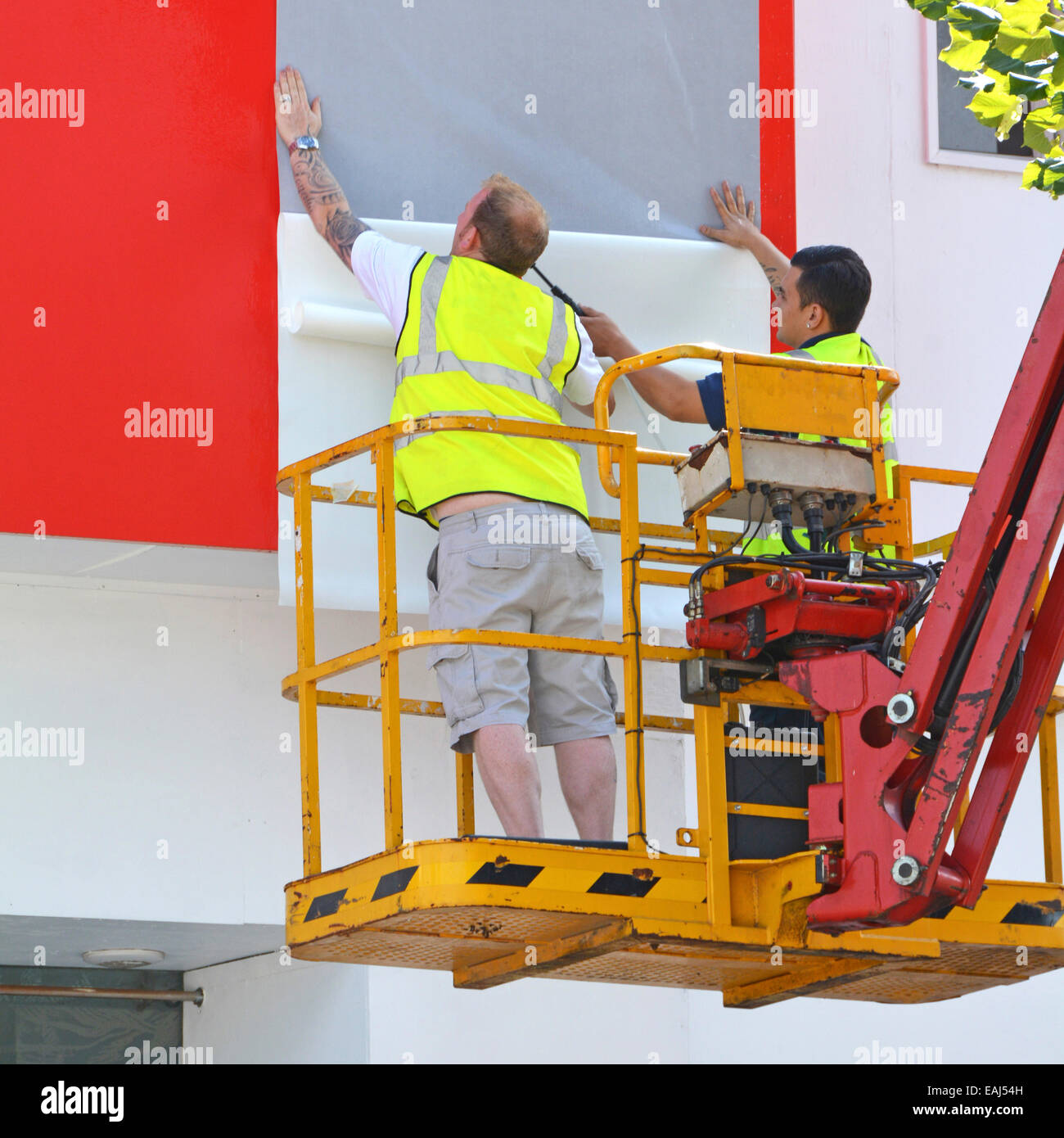 Cherry picker access platform in use by workmen fixing sheets of graphics forming a big advert display on side of - Stock Image