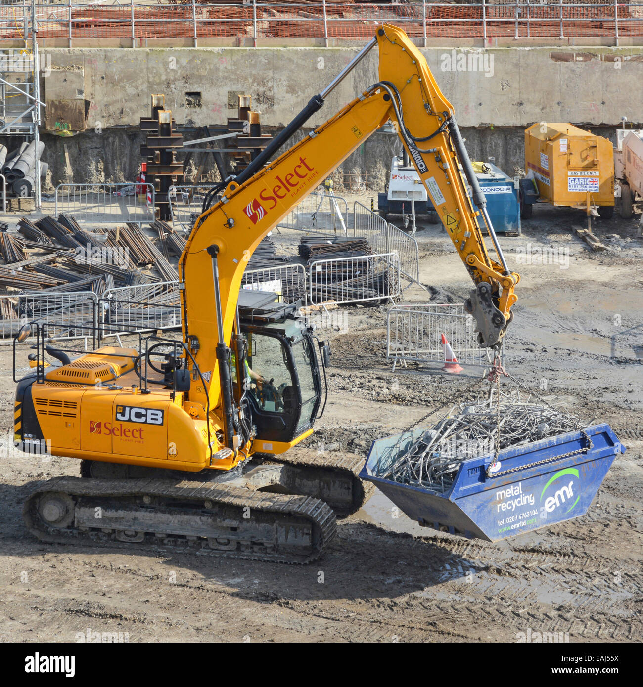 JCB excavator digger carrying recycling skip of steel bars across basement construction site - Stock Image