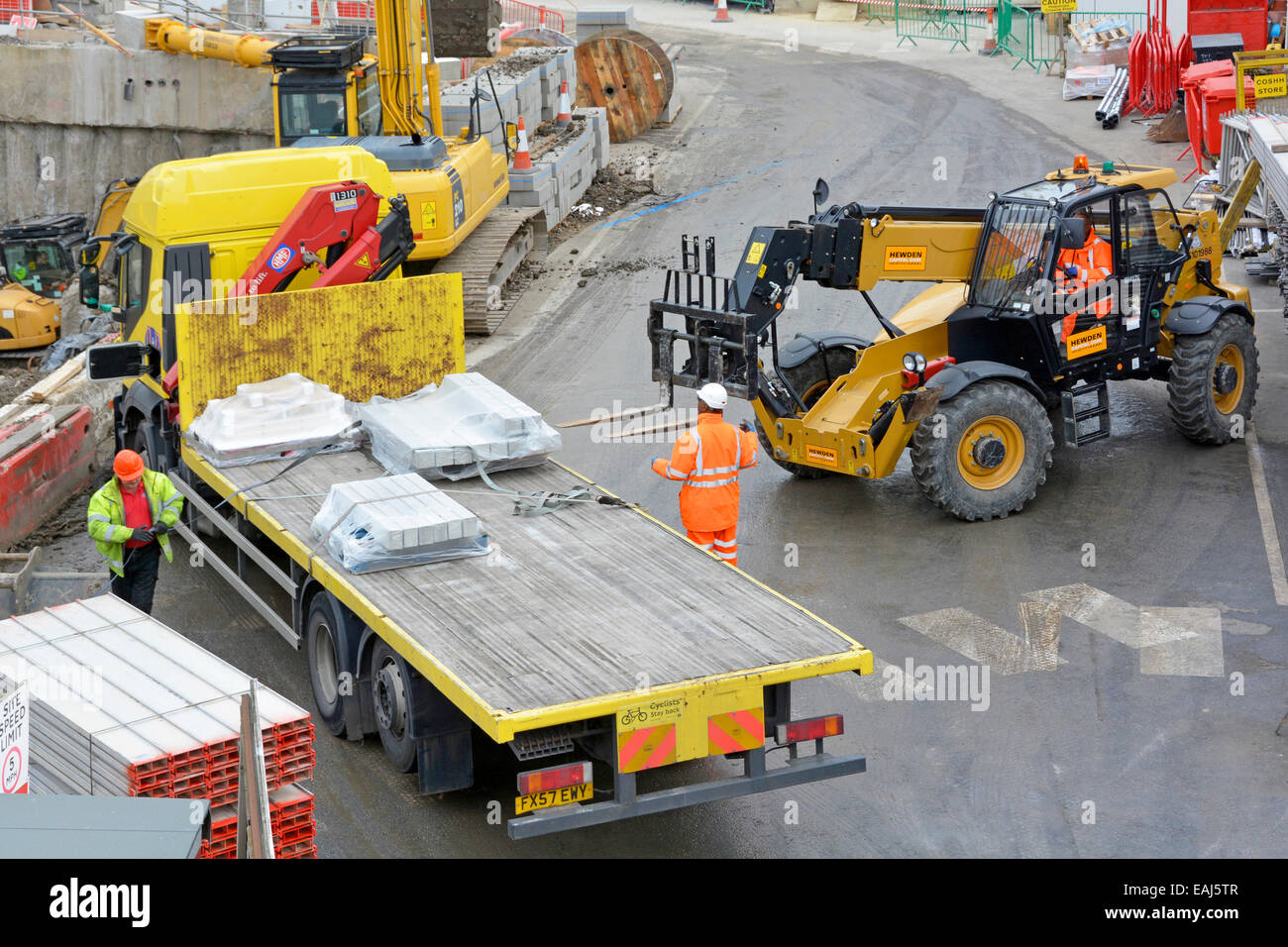 Aerial view building construction site forklift truck to unload flatbed delivery lorry workmen wearing hard hat & high visibility jacket London UK Stock Photo