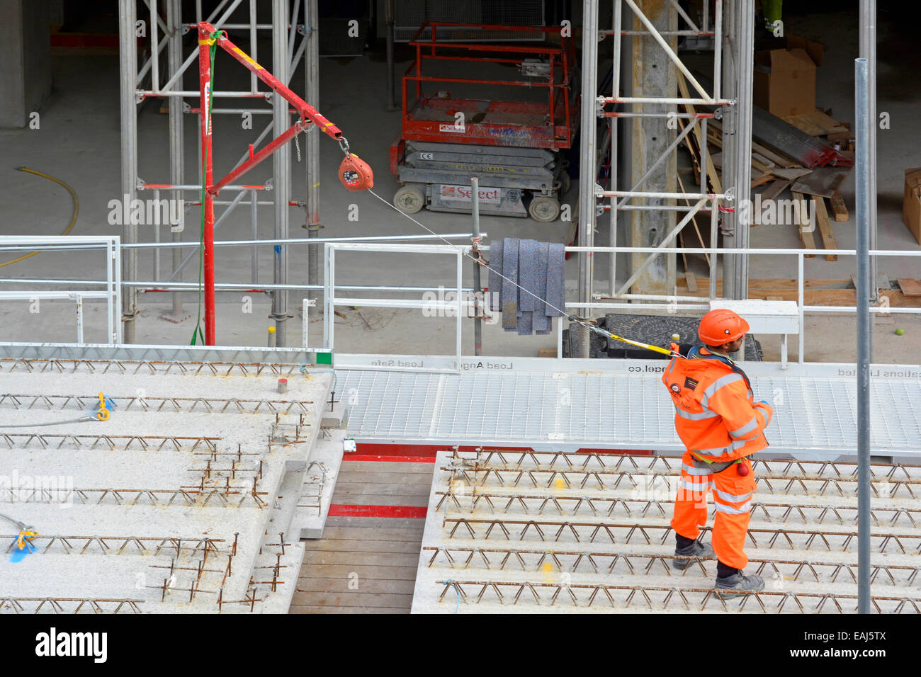 Fall prevention restraint system in use by workman on raised platform with safety harness worn under high visibility - Stock Image
