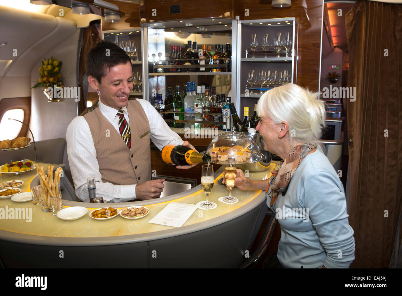 Emirates Airline, barman pouring champagne in bar of A380 Business Class cabin - Stock Image