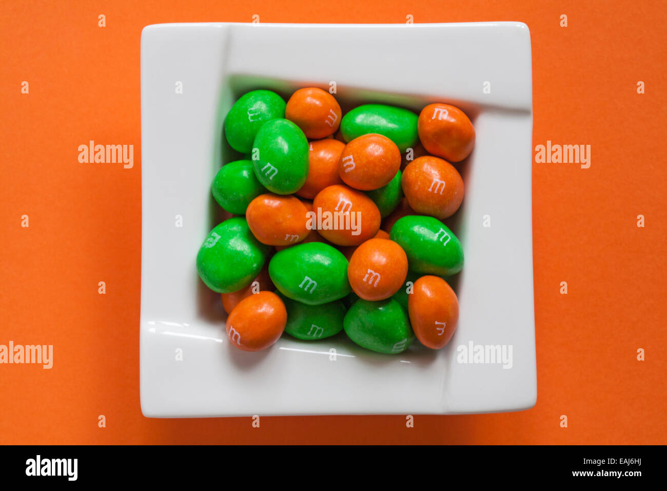 limited edition peanut M&Ms for Halloween in bowl isolated on orange coloured  background - looking down on - Stock Image