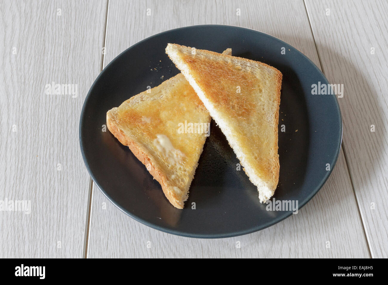 Piece of buttered hot toast, cut into triangles on a plate - Stock Image