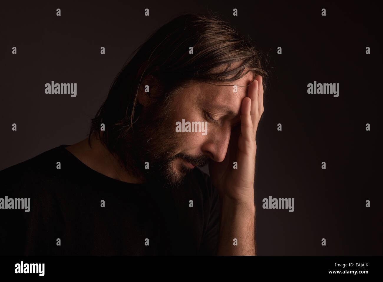 Bearded adult man with migraine headache, low key portrait - Stock Image