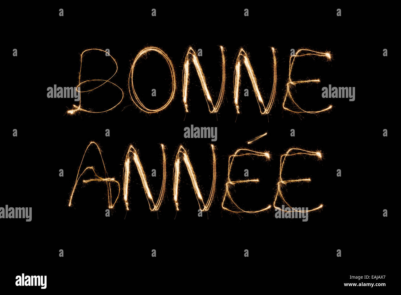 bonne annee french happy new year written with a sparkler isolated on black background