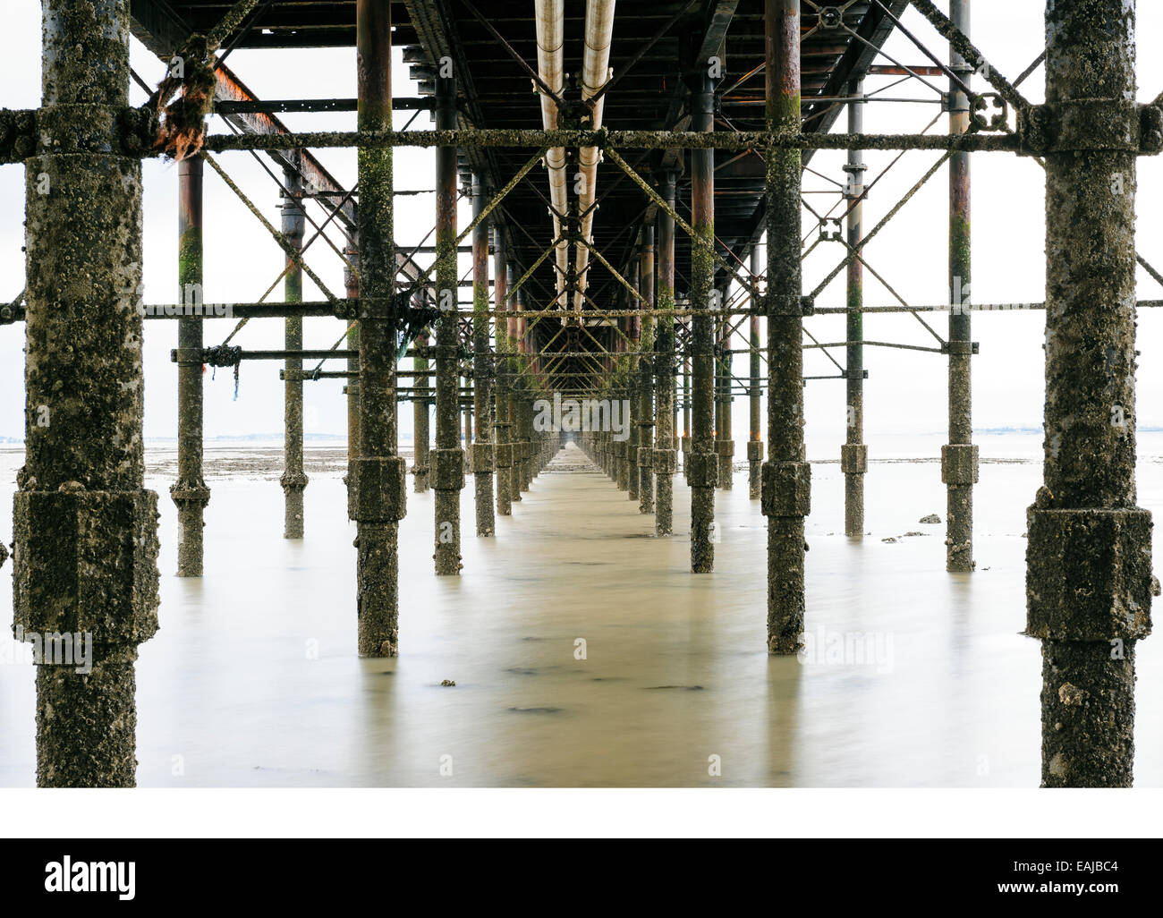 Underneath the iron, barnacle encrusted structure of Southend on sea's pier. - Stock Image
