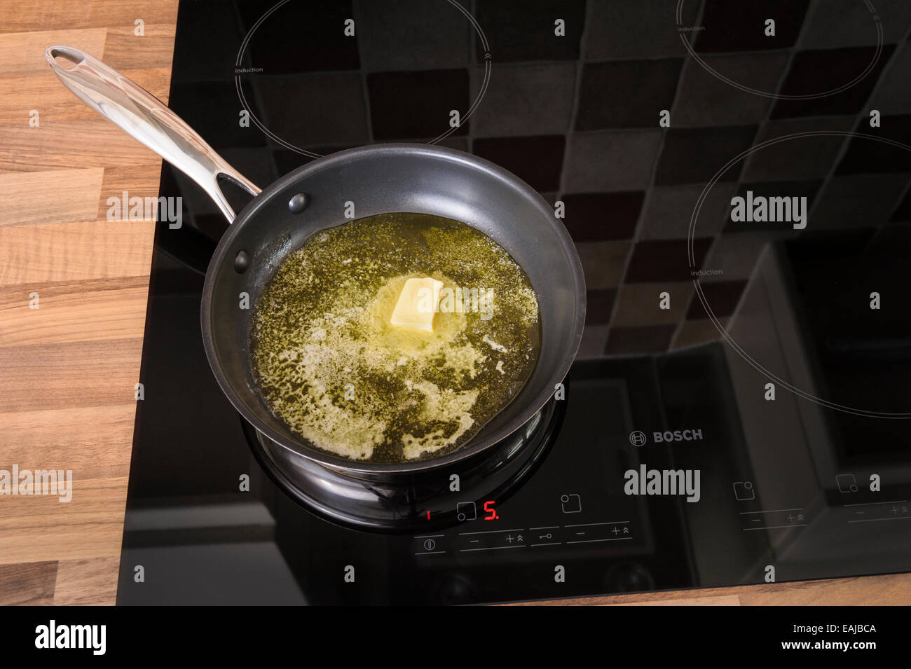 Butter melting in a frying pan, on an induction hob.Unhealthy, cholestrol. - Stock Image