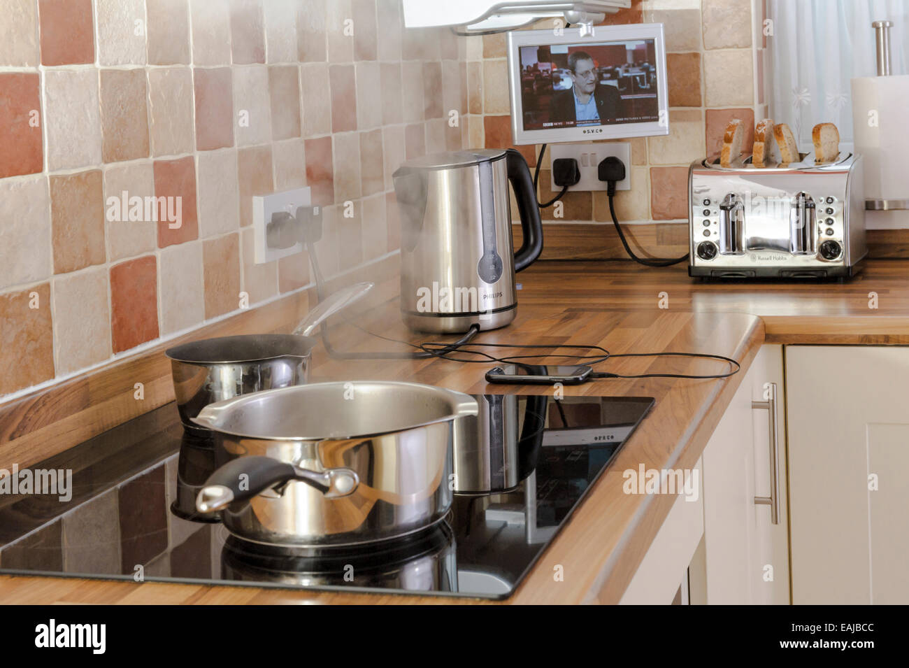 Many appliances being used in a modern kitchen.Heavy electrical consumption. - Stock Image