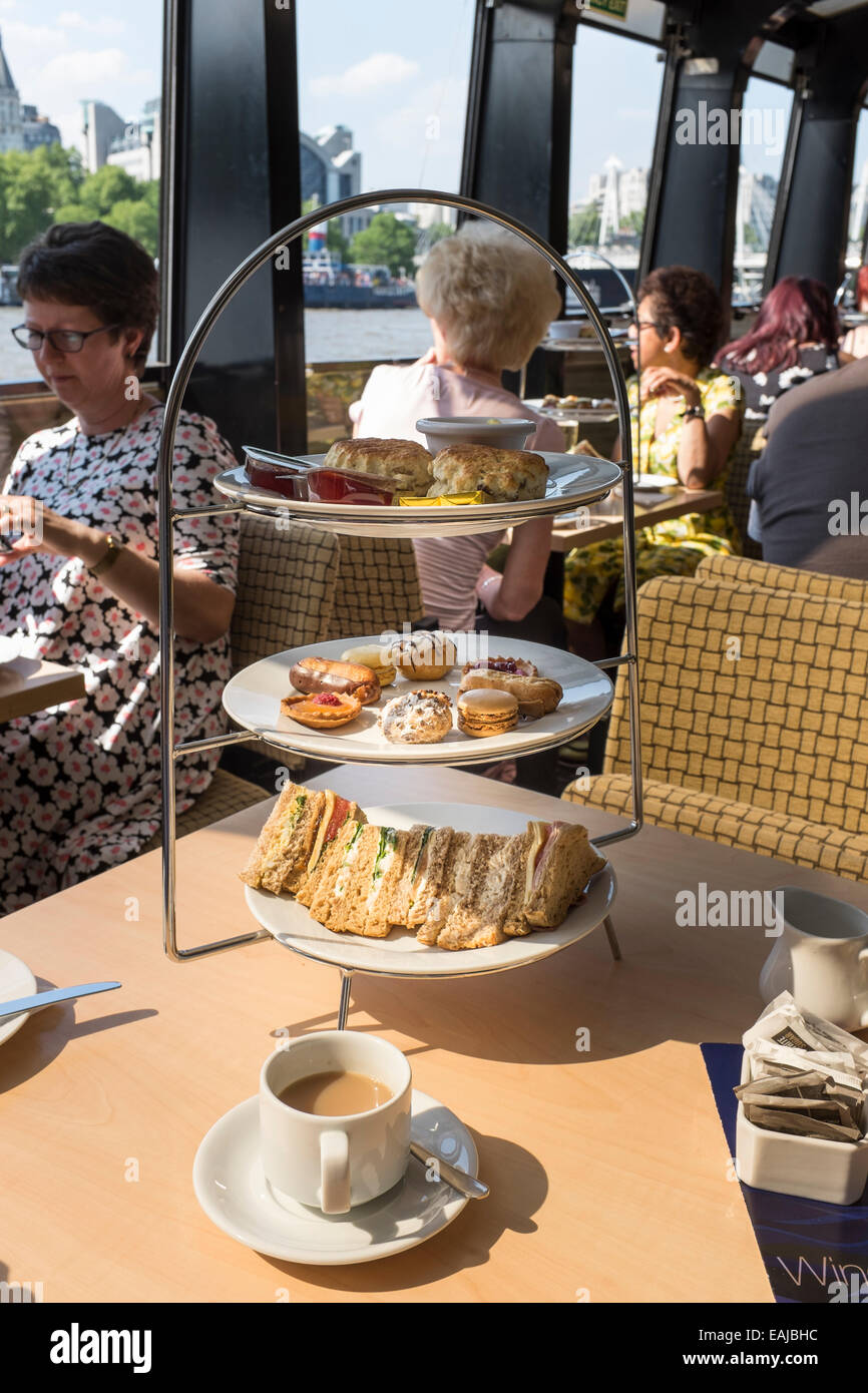 Sandwiches, cakes and scones with a cup of tea are all part of an afternoon boat trip on the River Thames. - Stock Image