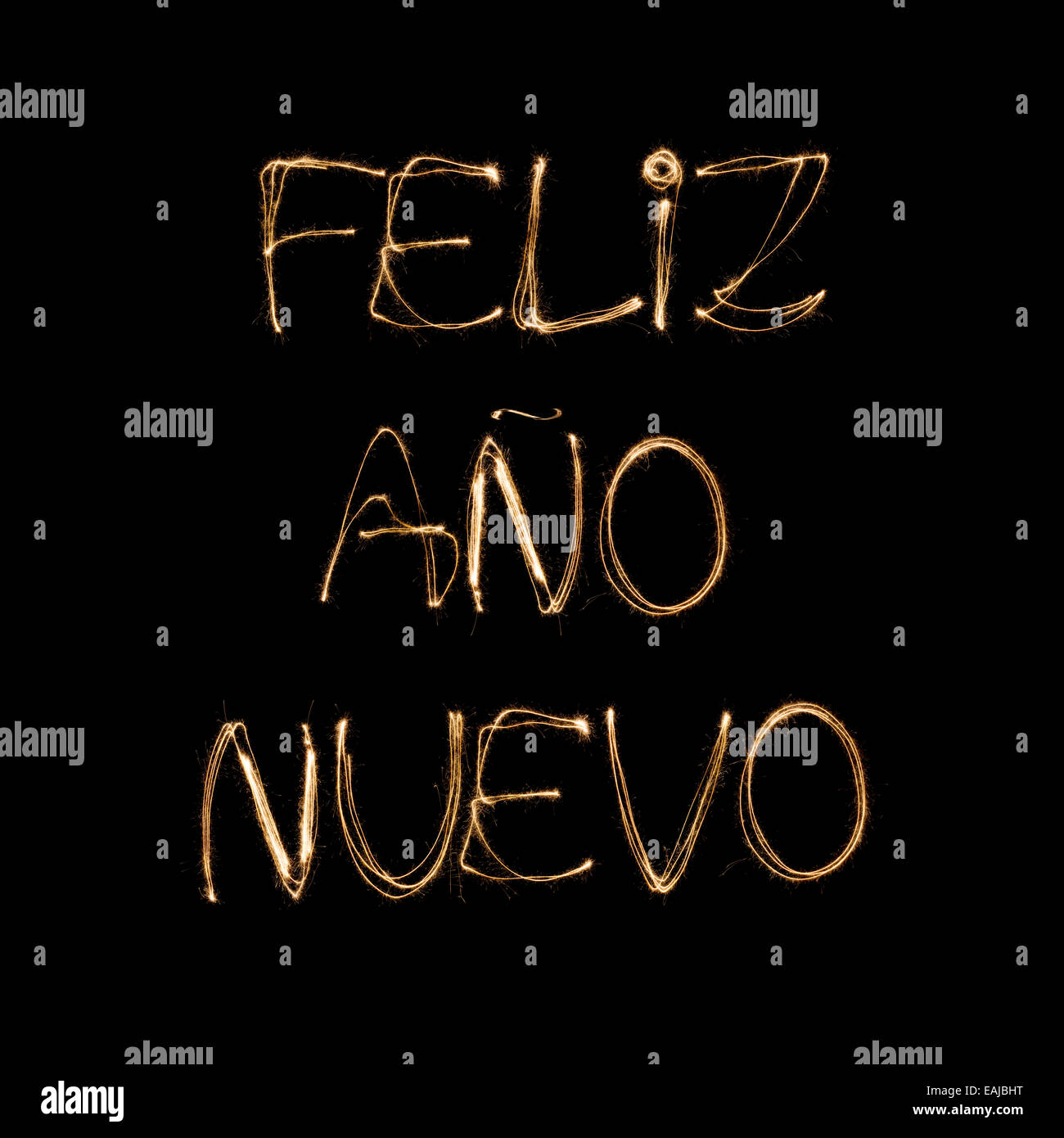 Feliz Ano Nuevo (Spanish Happy new Year) written with a sparkler isolated on black background - Stock Image