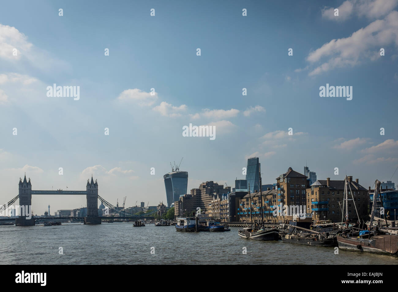 House boats and barges moored at Wapping on the north bank of the River Thames with the City of London and Tower Stock Photo