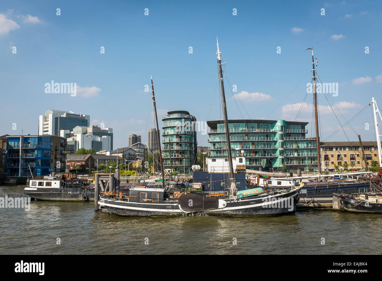 House boats and barges moored at Wapping on the north bank of the River Thames with modern apartment buildings behind. Stock Photo