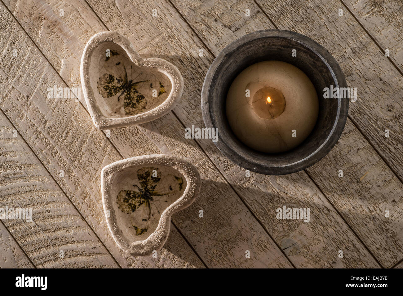 Two heart decorations on a white washed wooden table next to a lit candle in a  stoneware pot all in low directional - Stock Image