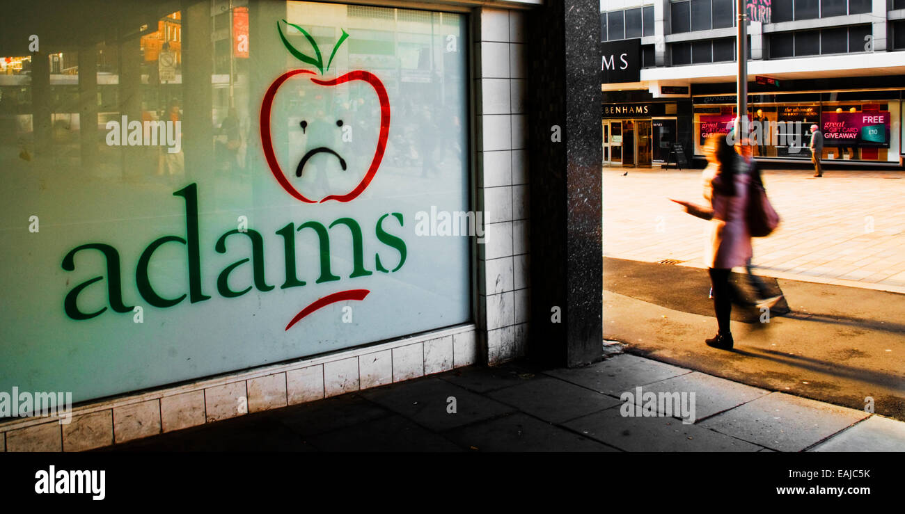 A woman walks past graffiti of a closed branch of Adams children's wear store on Moor Street in Sheffield city - Stock Image