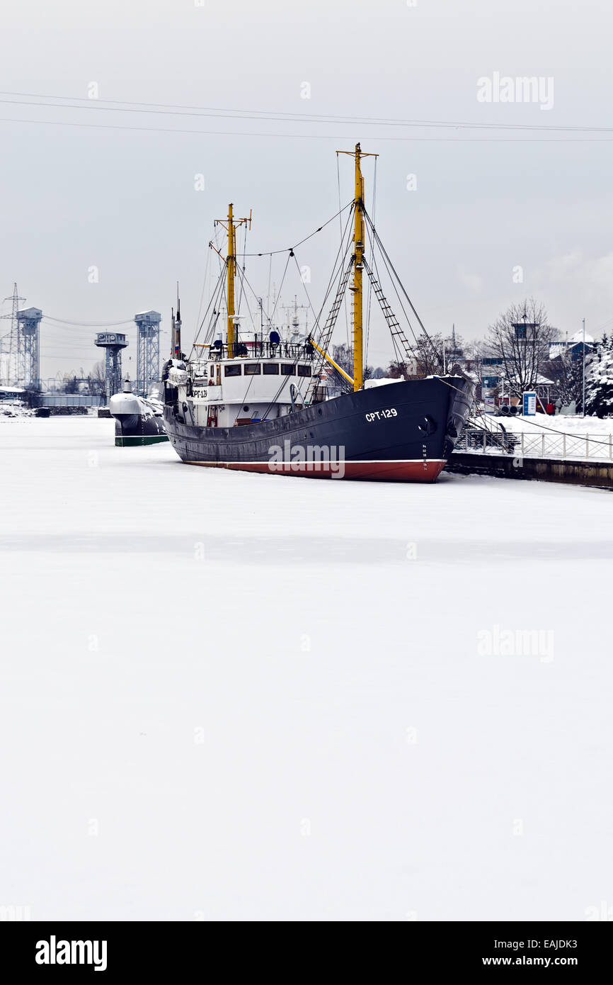 Average fishing trawler,  bound with ice. Embankment of Peter the Great, Kaliningrad (until 1946 Koenigsberg), Russia Stock Photo