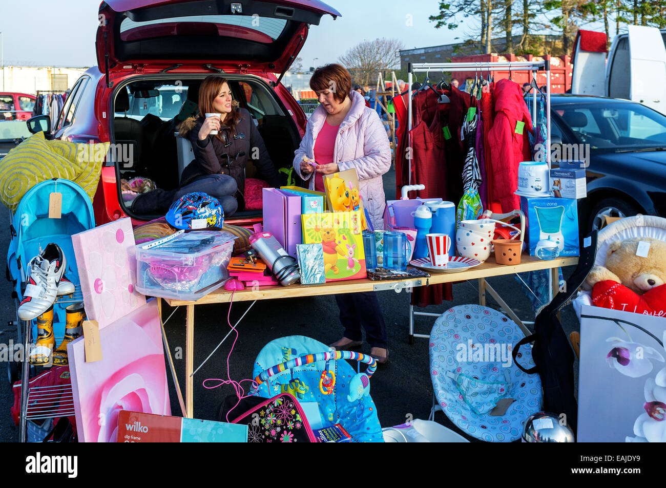 Two women running a stall at the car boot sale, Ayr, Ayrshire, Scotland, UK - Stock Image