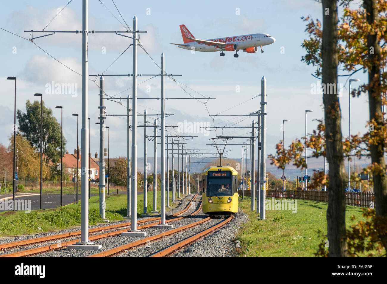 Digital montage of an aircraft above a Metrolink tram, on the Airport Line near Manchester Airport.  Manchester, Stock Photo