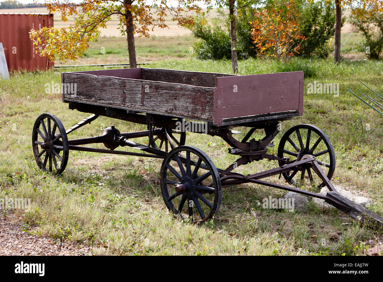 old wooden and metal farm wagon made from vehicle wheels and axle in depression era leader Saskatchewan Canada - Stock Image
