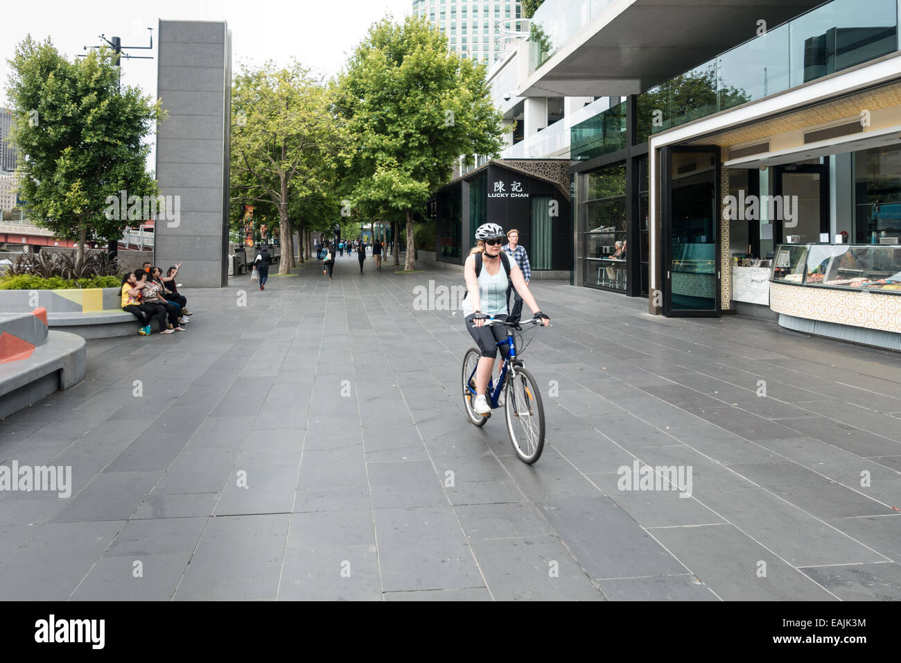 Female bicycle rider on Southbank promenades, Yarra River, Melbourne. - Stock Image
