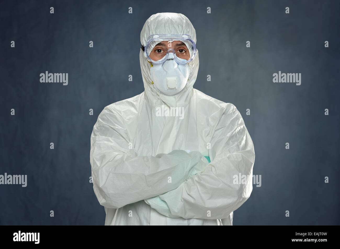 Man in Hazmat suit, protective gloves and goggles inside tent - Stock Image