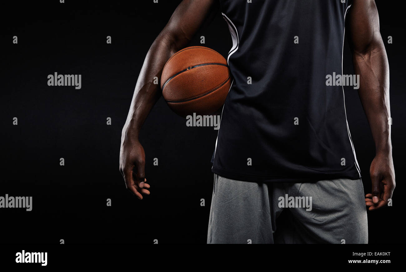 Cropped image of Afro-American basketball player holding a ball against dark background - Stock Image