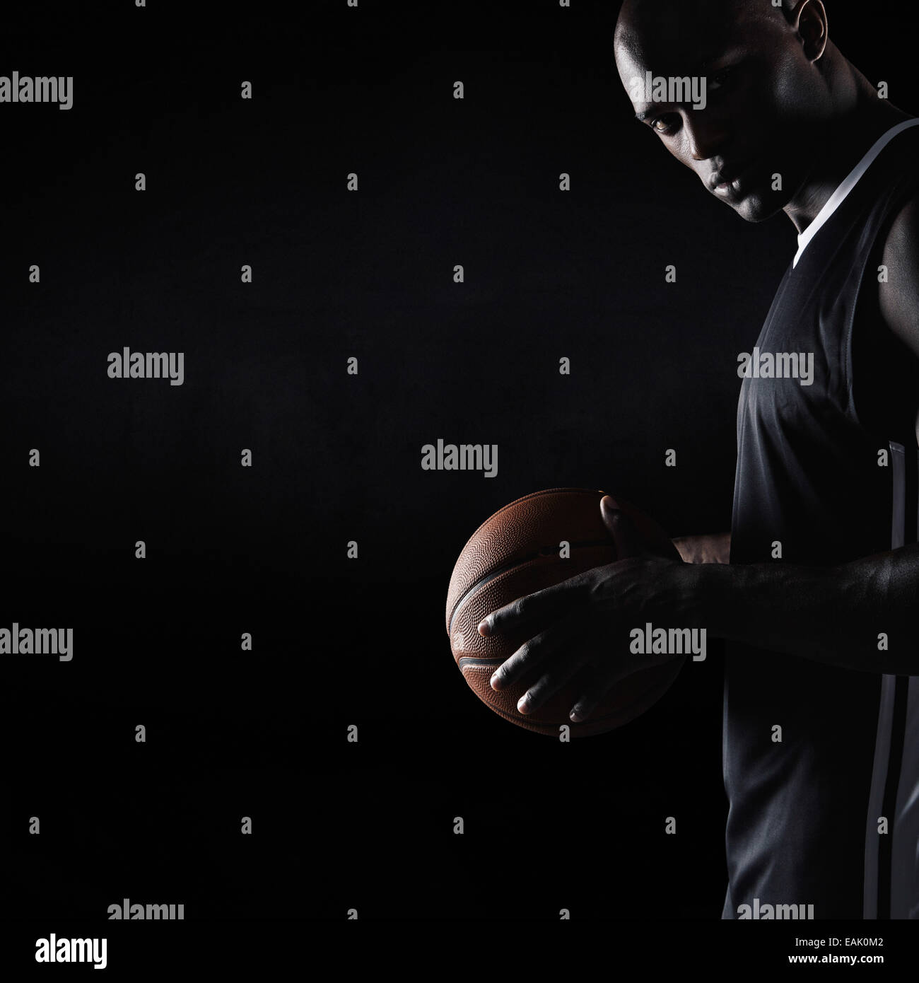 Studio shot of strong young man holding basketball looking at camera with copy space. African basketball player. - Stock Image